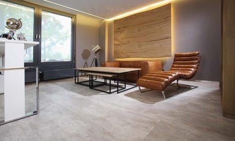wineo Bodenbelag Steinoptik im Wartebereich mit Lederstühlen