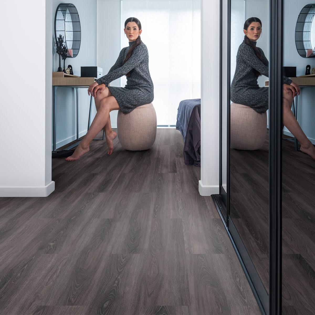 wineo Bodenbelag im Schlafzimmer mit Frau und eleganter Einrichtung